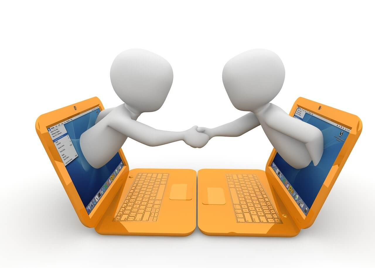 Two people coming out of laptop screens shaking hands